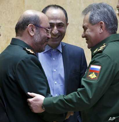 Mideast Iran Russia: FILE -- In this Feb. 16, 2016 file photo, Russian Defense Minister Sergei Shoigu, right, and Iranian Defense Minister Gen. Hossein Dehghan shake hands during their meeting in Moscow, Russia.