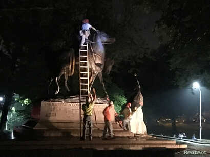 """Workers remove the monuments to Robert E. Lee, commander of the pro-slavery Confederate army in the American Civil War, and Thomas """"Stonewall"""" Jackson, a Confederate general, from Wyman Park in Baltimore, Maryland, U.S. Aug. 16, 2017."""