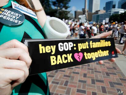FILE - Samantha Montgomery of Denver holds up a sign during an immigration rally and protest in Civic Center Park Saturday, June 30, 2018, in downtown Denver.