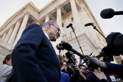 As a bitterly divided Congress moves toward a government shutdown, Senate Minority Leader Chuck Schumer, D-N.Y., center, speaks to the media outside the Capitol after meeting with President Donald Trump, Jan. 19, 2018, in Washington.