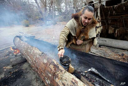Mashpee Wampanoag Phillip Wynne pours water to control fire and temperatures while making a boat, from a tree at the Wampanoag Homesite at Plimoth Plantation, in Plymouth, Mass.