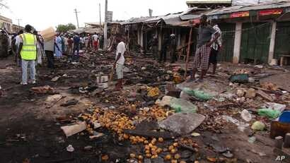 People gather at the scene of a car bomb explosion, at the central market, in Maiduguri, Nigeria, July 2, 2014.