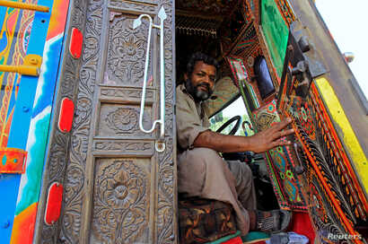 A driver holds open the door of the carved wood cab of his decorated truck in Faisalabad, Pakistan, May 4,  2017.