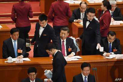 FILE - Chinese President Xi Jinping (C) looks on as his tea cup is replenished during the second plenary session of the National People's Congress in Beijing's Great Hall of the People on March 9, 2018.
