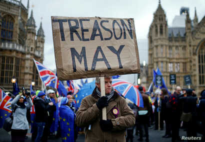 FILE - A pro-Brexit protester holds a banner as anti-Brexit protesters demonstrate outside the Houses of Parliament, ahead of a vote on Prime Minister Theresa May's Brexit deal, in London, Britain, January 15, 2019.