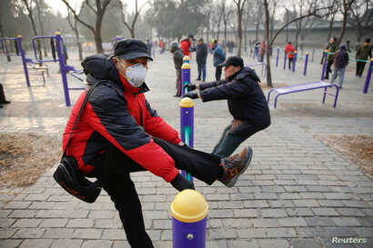 A man wearing a face mask exercises in a park despite a red alert issued for air pollution in Beijing, China, Dec. 18, 2016.