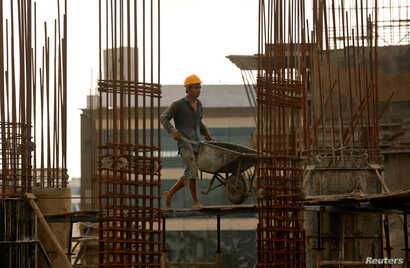 FILE - A worker pushes a wheelbarrow to collect cement at a construction site of a residential building in Mumbai, India, Aug. 31, 2018.