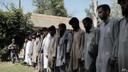 Arrested Islamic State fighters stand outside Afghan police headquarters in Nangarhar, Afghanistan