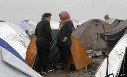 Syrian refugee women look on, standing in the mud between tents in an improvised camp on the border line between Macedonia and Serbia near the northern Macedonian village of Tabanovce, March 11, 2016.