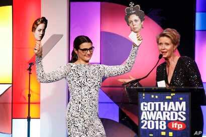 """Actress Rachel Weisz, left, holds photos of her co-stars Emma Stone and Olivia Colman from the movie """"The Favorite"""" as she accepts a special honor from Cynthia Nixon at the 28th annual Gotham Awards, Nov. 26, 2018, in New York."""