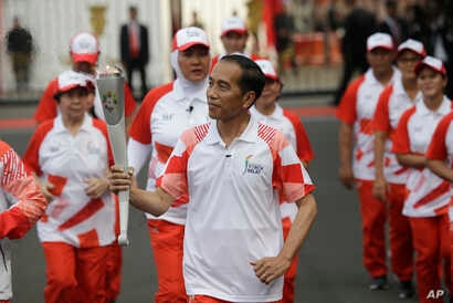 """Indonesian President Joko """"Jokowi"""" Widodo, center, holds the Asian Games torch as he runs during an independence day ceremony at Merdeka Palace in Jakarta, Indonesia, Aug. 17, 2018. Jokowi announced Indonesia would bid for the 2032 Olympic Games."""