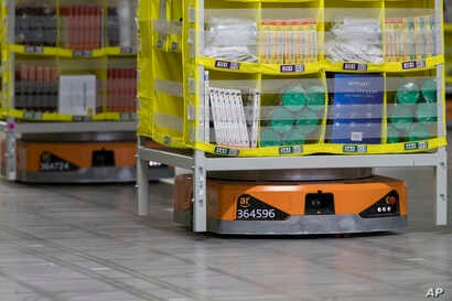 FILE - Pods full of merchandise are moved around the floor by robotic drives, named Amazon robots, at the Amazon fulfillment center in the Staten Island borough of New York, Dec. 5, 2018.