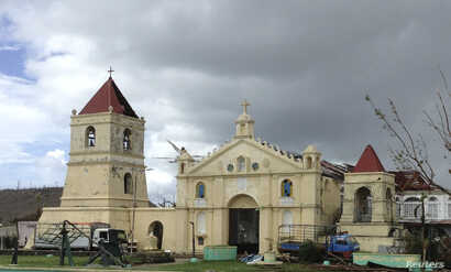 FILE - In Balangiga, the Roman Catholic belfry rises from the rubble, a battered symbol of resistance for a people with mixed feelings about the U.S. military now helping them survive. The town built the belfry in 1998 in the hope that the United Sta...