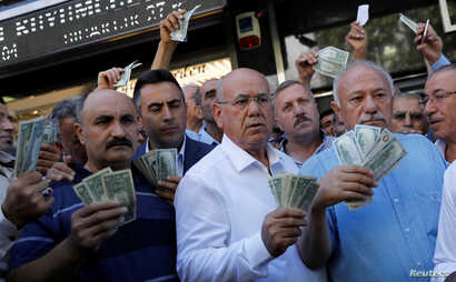 Businessmen holding U.S. dollars stand in front of a currency exchange office in response to the call of Turkish President Tayyip Erdogan on Turks to sell their dollar and euro savings to support the lira, in Ankara, Aug. 14, 2018.