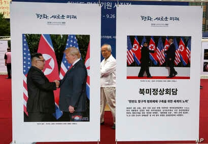 Photos of the summit between U.S. President Donald Trump and North Korean leader Kim Jong Un are displayed during a photo exhibition to wish for peace on the Korean Peninsula in Seoul, South Korea, Wednesday, Sept. 19, 2018.