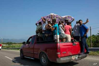 Joel Eduardo Espinar stands on the bumper of a truck as his family and others arrive in Arriaga, Mexico. Four of Espinar's friends in Honduras died from stabbings, and his wife was robbed twice at knifepoint on her way home from the stand where she s...