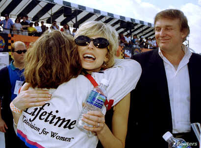 FILE - Marla Maples and her husband Donald Trump greet race driver Lyn St. James prior to the inaugural Indy 200 race at Walt Disney World.