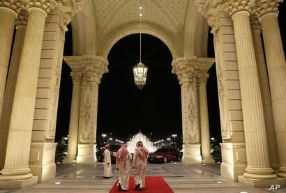 FILE - Saudi men walk at the entrance to the Ritz-Carlton Hotel, in Riyadh, Saudi Arabia, March 4, 2013.  Dozens of elite detainees are reportedly being held in a well-guarded ballroom of the hotel as part of a sweeping corruption probe.
