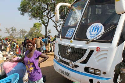 FILE - a women stands in front of a UNHCR passenger bus next to a refugee registration site near Bibi bidi, Uganda. About 440,000 people have fled South Sudan's spiraling civil war into Uganda this year alone.
