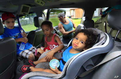 Estanislao Fabian loads the car while Jordan Fabian, 6, and Jaylah Cole, 6, comfort Jaden Fabian, 1, as they evacuate their home in advance of Tropical Storm Isaac in Plaquemines Parish, La.,  Aug. 28, 2012.