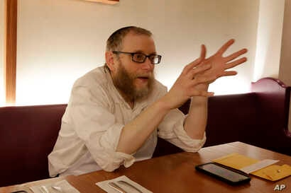 Daniel Cohen, owner of Pinskers Books and Judaica, and the adjoining cafe, sits at a table before dinner service, Nov. 20, 2018, in the Squirrel Hill neighborhood of Pittsburgh.