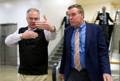 Sen. Tim Kaine, D-Va., speaks with Sen. Mark Warner, D-Va., as they walk to their offices Jan. 20, 2018, on Capitol Hill in Washington. Republicans and Democrats showed no signs of ending their standoff over immigration and spending Saturday as Ameri...