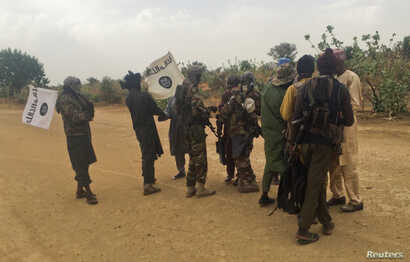 Boko Haram militants (in camouflage) embrace and shake hands with Boko Haram prisoners, released in exchange for a group of 82 Chibok girls, who were held captive for three years by Islamist militants, near Kumshe, Nigeria, May 6, 2017.