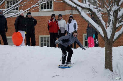 A group of adults and children enjoy an afternoon of sledding and snowboarding on a hill on the campus of Wake Forest University in Winston-Salem, North Carolina, Jan. 17, 2018.