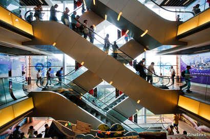 FILE - Tourists descend on an escalator inside a shopping mall at the Peak in Hong Kong, China, Aug. 4, 2017.