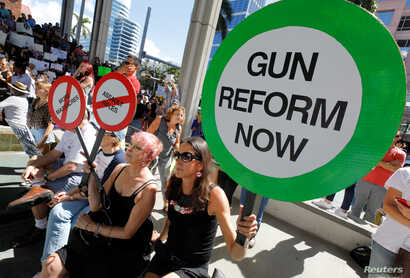 Protesters hold signs as they call for a reform of gun laws three days after the shooting at Marjory Stoneman Douglas High School, at a rally in Fort Lauderdale, Florida, Feb. 17, 2018.