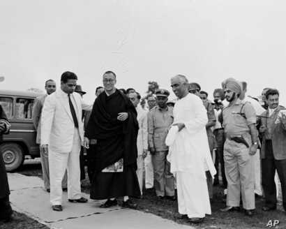 FILE - An unidentified Indian official, right, greets Tibetan spiritual leader Dalai Lama, left, at a military camp on the border of Assam and the Northeast Frontier Agency area, April 18, 1959, shortly after the Dalai Lama's arrival in India.