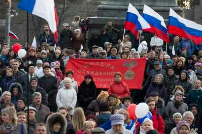 People gather with Russian and Crimean flags awaiting a concert where Russian President Vladimir Putin later made an appearance in Sevastopol, Crimea, March 14, 2018.