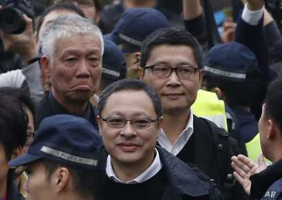 Three protest leaders, from right, Chan Kin-man, Benny Tai Yiu-ting and Chu Yiu-ming walk towards the police station in Hong Kong as they surrender to police, Dec. 3, 2014.