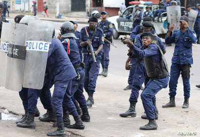 FILE - Policemen react after a protester threw a stone from Notre Dame Cathedral compound in Kinshasa, Democratic Republic of Congo, Feb. 25, 2018.