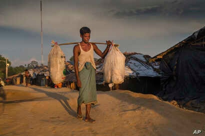 A Rohingya Muslim man Bodi-Ur-Rehman stops for a photograph as he arrives carrying his belongings at Kutupalong refugee camp, Bangladesh, Sept. 15, 2017.