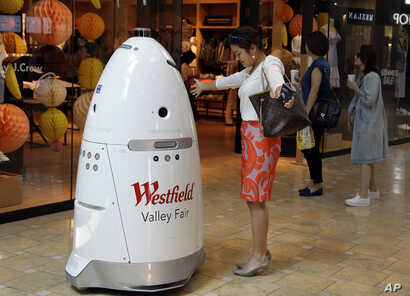 FILE - Sophie Li of Cupertino, California, offers to dance with a K5 robot made by Knightscope Inc., at Westfield Valley Fair shopping center in San Jose, California, June 26, 2017.