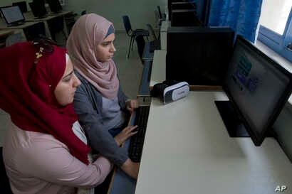 """Wassan al-Sayyed,17, right and Massa Halawa, 16 run the team's virtual reality game """"Be a Fire Fighter"""" in the West Bank city of Nablus, Aug. 2, 2018. Four Palestinian high school friends are heading to California this week to pitch their mobile app ..."""