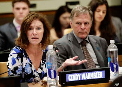 Fred Warmbier, right, listens as his wife Cindy Warmbier, speaks of their son Otto Warmbier, an American who died last year, days after his release from captivity in North Korea, May 3, 2018, at the U.N.