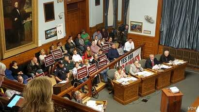 """Lowell residents attended the city council session with signs """"Lowell High School Downtown"""" in early June, as the council debated on whether or not to renovate or move Lowell High School to a different location. (Courtesy photo of Common Wealth M..."""