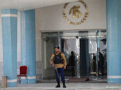 An Afghan security guard stands at the entrance gate of the Intercontinental Hotel after an attack in Kabul, Afghanistan Jan. 23, 2018