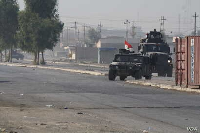 Army vehicles race back from the battle front deeper in the city in Gogjali, Mosul, Iraq, Nov. 7, 2016.
