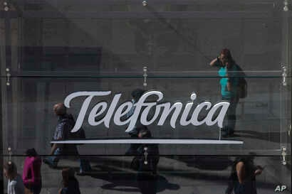 People are reflected in a glass sign of a Telefonica building in Madrid, Spain, May 13, 2017. The Spanish government said several companies including Telefonica had been targeted in ransomware cyberattack that affected the Windows operating system of...