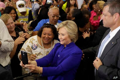Democratic presidential candidate Hillary Clinton meets with attendees during a campaign stop at the Frontline Outreach Center in Orlando, Florida, Sept. 21, 2016.