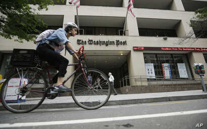 FILE - A bicyclist rides past The Washington Post building, Aug. 6, 2013, in Washington.