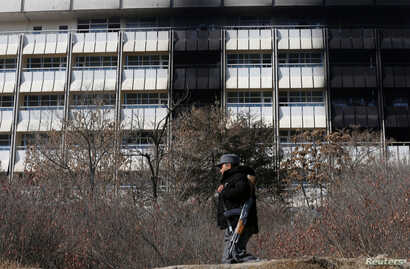 An Afghan policeman walks in front of the Intercontinental Hotel a day after an attack in Kabul, Afghanistan, Jan. 22, 2018.