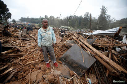 A man stands on the rubbles of his home after bulldozers demolished dozens of houses to make way for a new road in the Kibera slum in Nairobi, Kenya, July 23, 2018.