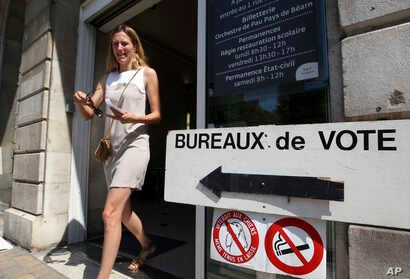 A woman leaves a polling station in the first round of parliamentary elections in Pau, southwestern France, June 11, 2017.