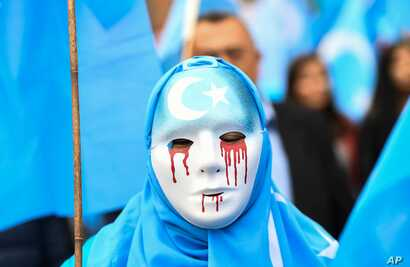 In Brussels on April 27, 2018, a person wearing a white mask with tears of blood takes part in a protest march of ethnic Uighurs asking for the European Union to call upon China to respect human rights in the Chinese Xinjiang region.