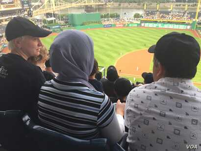 Michelle Boehm, a mentor and friend of Kazam Hashimi's family, attend Hello Neighbor's Refugee and Immigrant Night at PNC Park, a first for the Pittsburgh Pirates baseball organization, Aug. 1, 2017, in Pittsburgh, Penn.