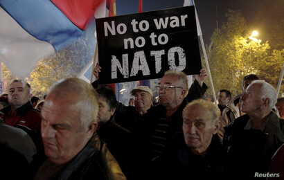 FILE - A demonstrator holds a sign during an anti-NATO protest in Podgorica, Montenegro, Dec. 12, 2015.